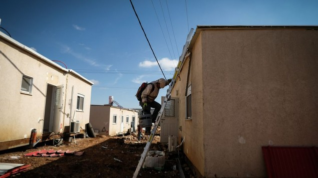 Construction workers work on clearing land for new caravans in the Jewish settlement of Ofra, in the West Bank, on January 29, 2017. (Yaniv Nadav/FLash90)