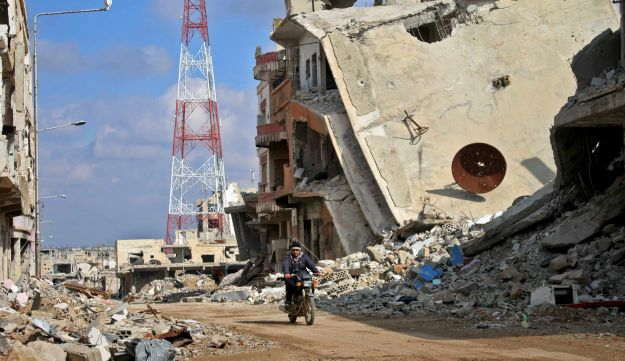 A Syrian man riding his motorcycle past damaged buildings in the southern city of Daraa, March 16, 2017.