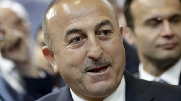 The Foreign Minister of Turkey Mevlut Cavusoglu speaks during a visit of the booth of Turkey at the tourism fair ITB in Berlin, Germany, Wednesday, March 8, 2017. (AP Photo/Michael Sohn)