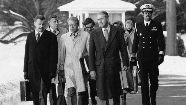 In this Feb. 14, 1979 photo, President Jimmy Carter, flanked by Secretary of State Cyrus, right, and his advisor on foreign policy, Zbigniew Brzezinski, left, walk toward a waiting helicopter to fly to the nearby Andrews Air Force Base, Md. (AP Photo/Bob Daugherty, File)