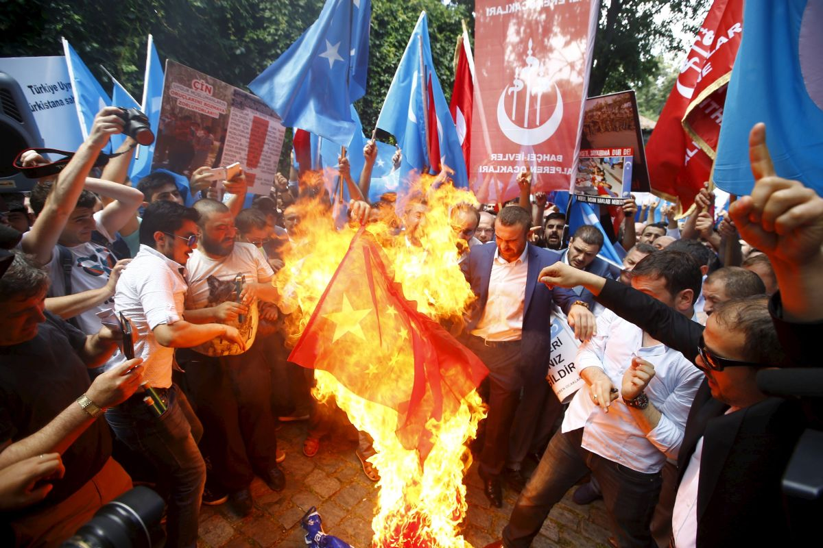 Demonstrators set fire to a Chinese flag during a protest against China near the Chinese Consulate in Istanbul