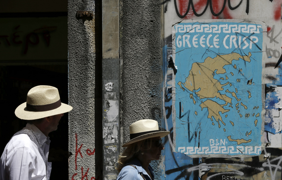 Pedestrians pass a poster depicting a map of Greece with the letter E being replaced by Euro symbols in Athens, Tuesday, May 2, 2017. (AP/Thanassis Stavrakis)