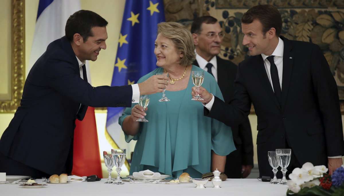 "French president Emmanuel Macron, right, Greek Prime Minister Alexis Tsipras, left, and Vlasia Pavlopoulou wife of the Greek President toast their drinks at the Presidential Palace in Athens, Thursday, Sept. 7, 2017. Standing at a Greek site where democracy was conceived, French President Emmanuel Macron called on members of the European Union to reboot the 60-year-old bloc with sweeping political reforms or risk a ""slow disintegration. (AP/Charalambos Gikas)"