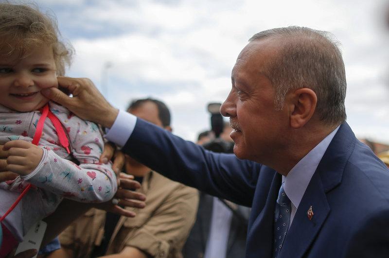 Ο Ερντογάν τσιμπά το μάγουλο μιας μικρής, έξω από το εκλογικό κέντρο όπου ψήφισε -Φωτογραφία: AP