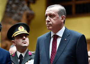 Recep-Tayyip-Erdogan-with-member-of-the-Turkish-Army-behind-him-image-via-Wikipedia-300×215